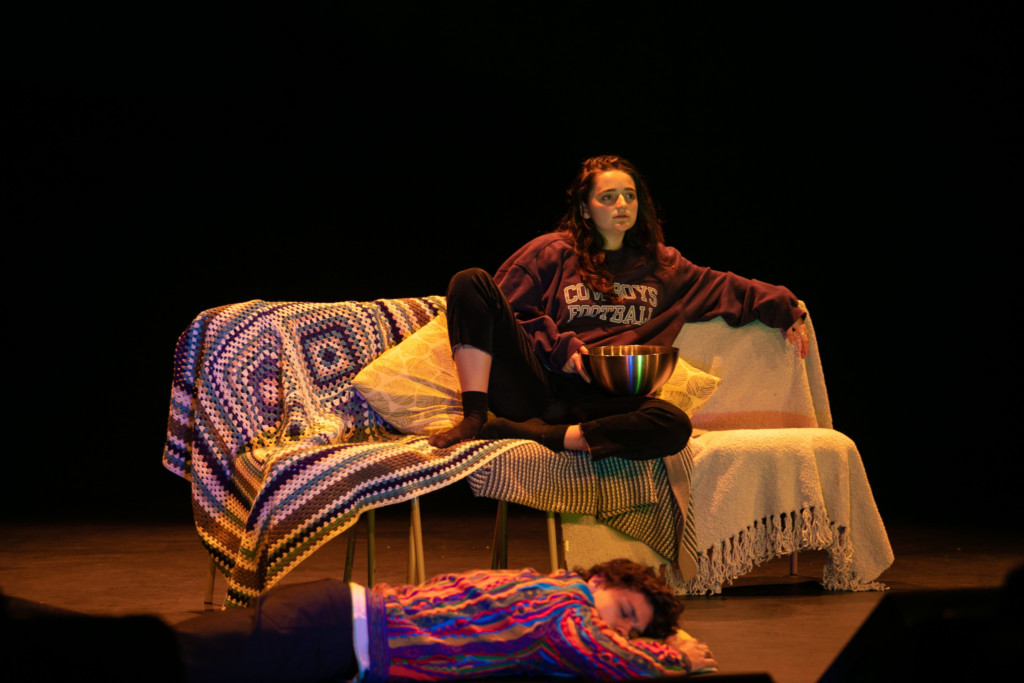 Young woman sitting on a couch on stage